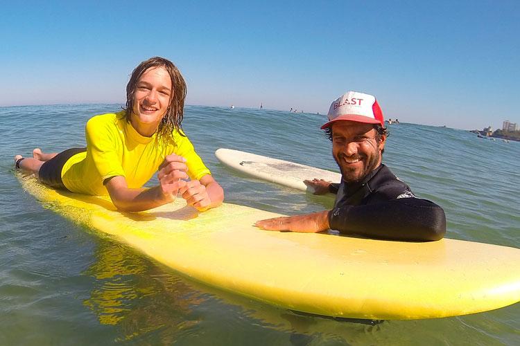 axel en el agua con un estudiante de surf a su lado en un softboard