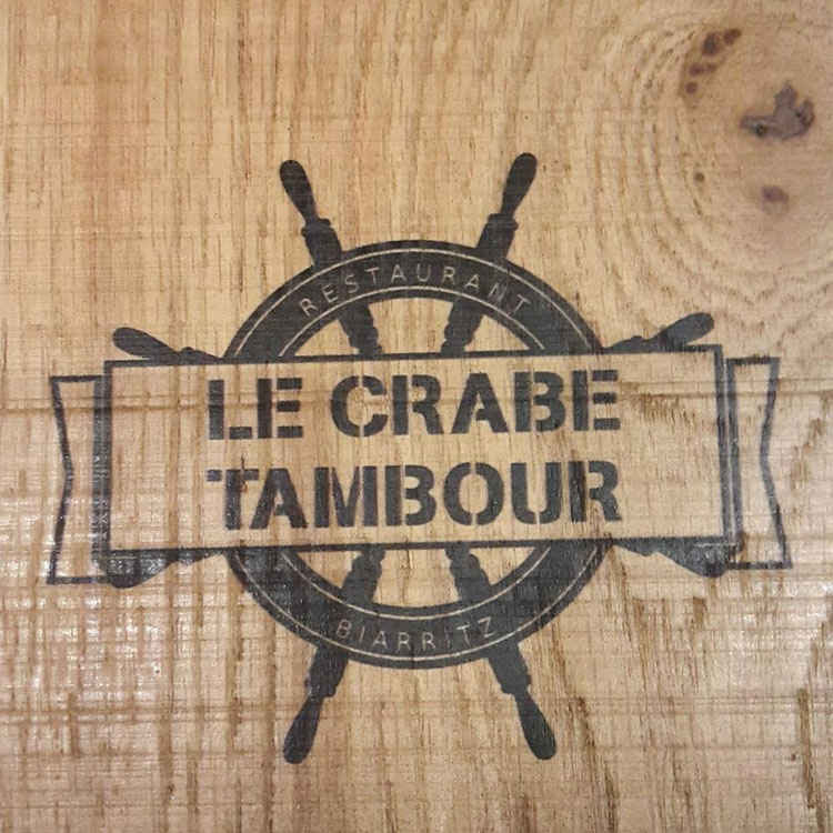 logo of le crabe tambour on wood